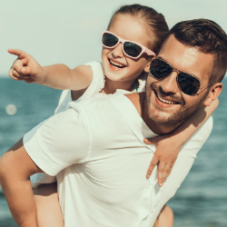 smiling father holds child on shoulders at beach